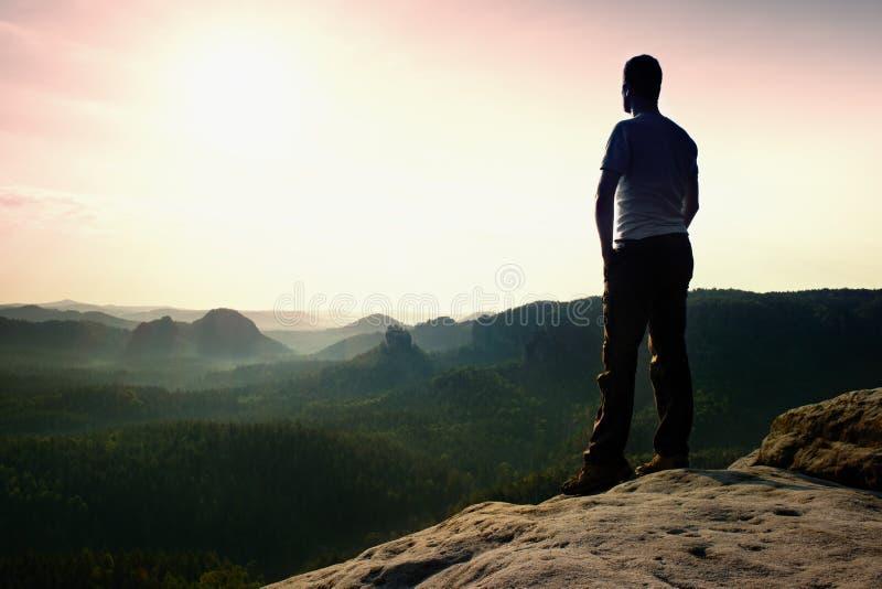 满足灰色衬衣和黑暗的长裤的高远足者 在观看锋利的岩石的边缘峰顶的Sprtsman下来环境美化 免版税库存照片