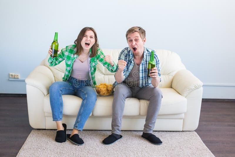 足球世界杯概念-朋友夫妇在沙发观看的体育比赛坐电视 库存照片