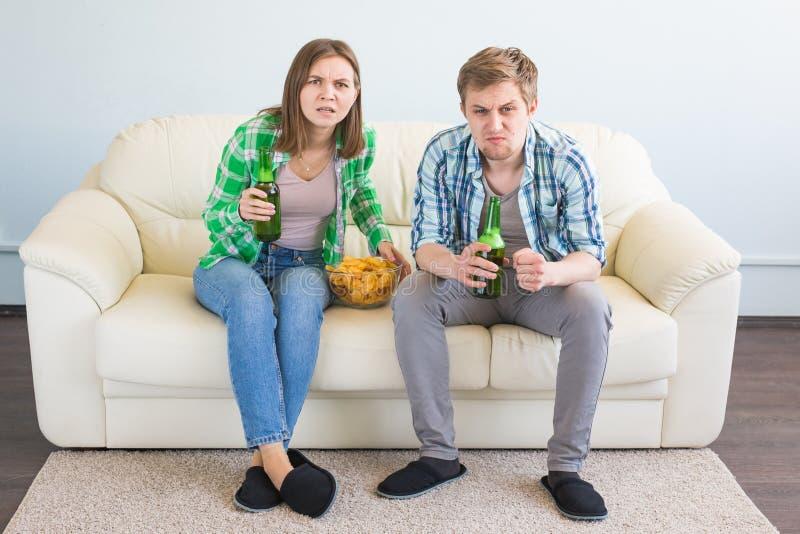 足球世界杯概念-看起来现代的夫妇在电视的激动的和愉快的观看的体育比赛 免版税库存图片