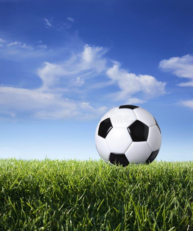 足球外形在草的反对蓝天 免版税库存图片