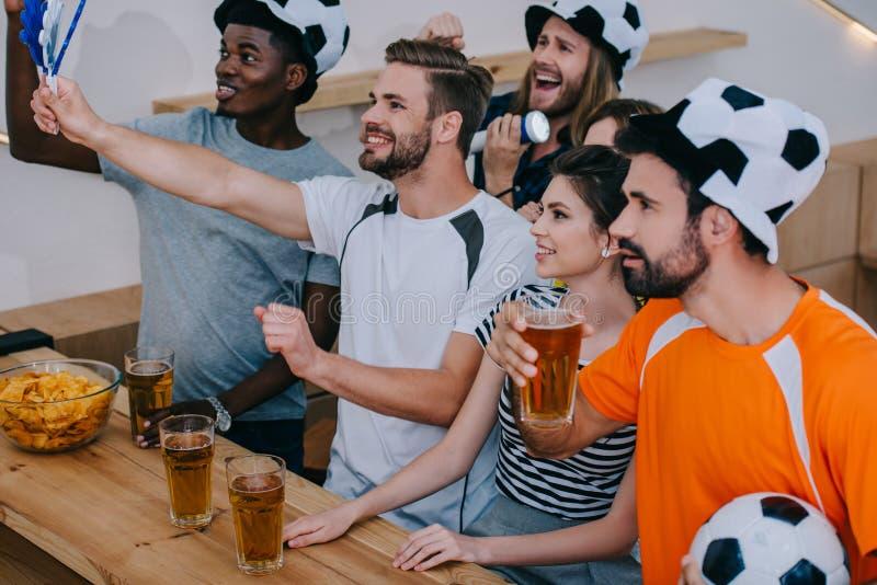 足球帽子的微笑的多文化朋友庆祝饮用的啤酒和观看足球赛的 免版税库存照片