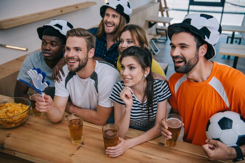 足球帽子的朋友喝啤酒和观看足球赛的愉快的多文化小组  免版税库存图片