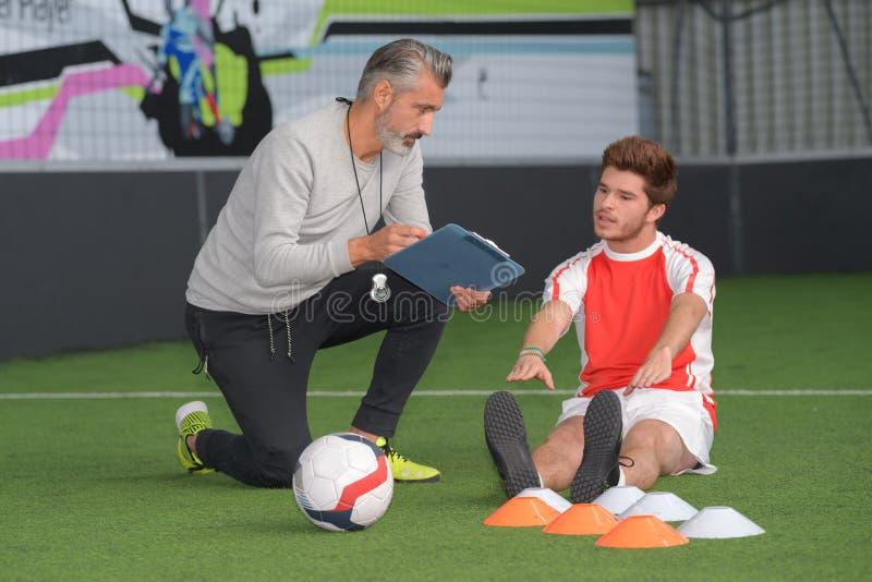 足球教练和足球运动员画象 图库摄影