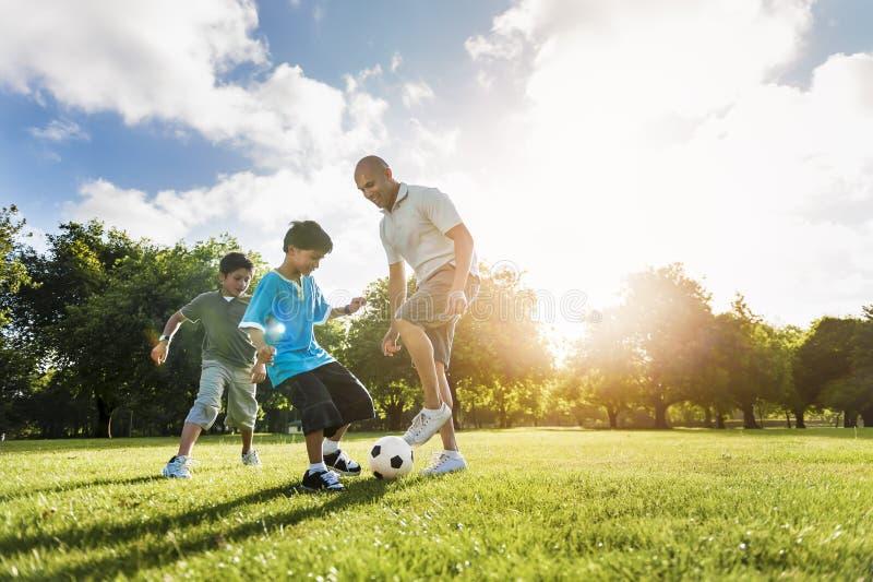 足球橄榄球场父亲儿子活动夏天概念 免版税库存照片
