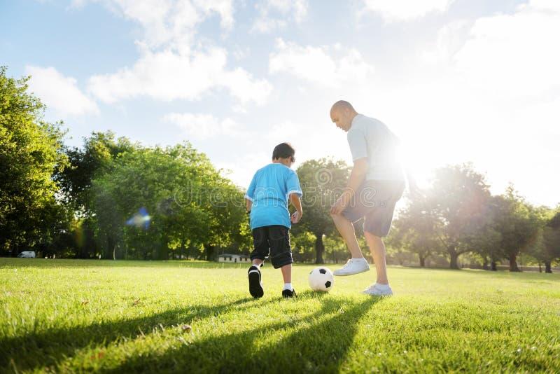 足球橄榄球场父亲儿子活动夏天概念 免版税库存图片