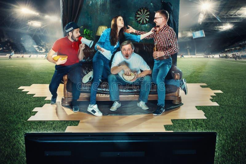 足球足球迷坐沙发和观看的电视在橄榄球场中间 库存图片