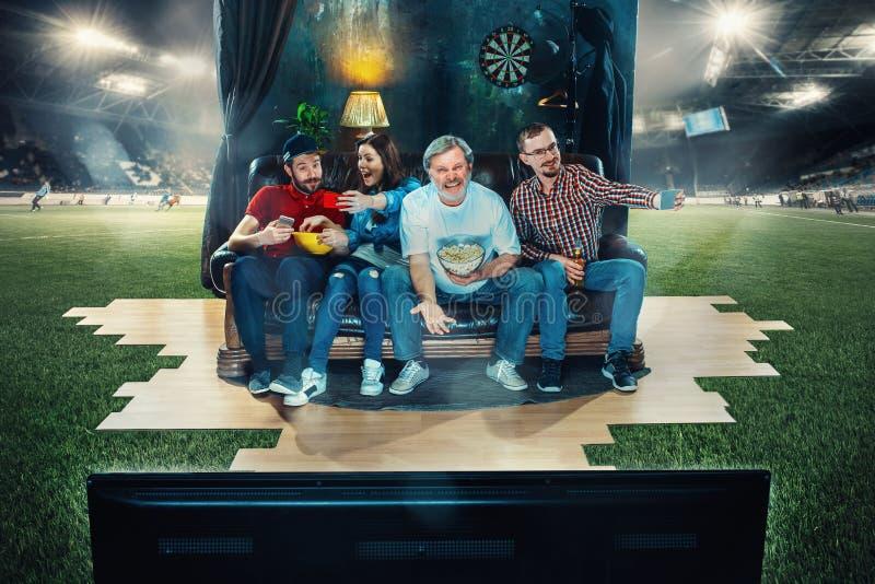 足球足球迷坐沙发和观看的电视在橄榄球场中间 免版税库存图片