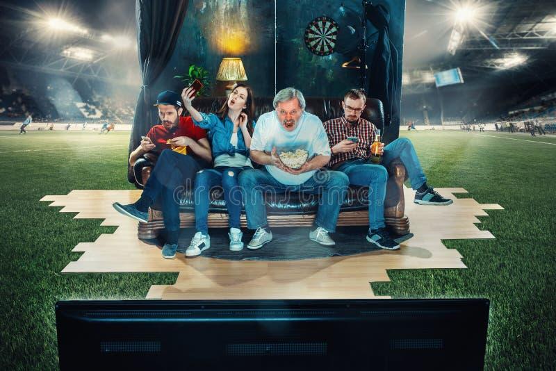 足球足球迷坐沙发和观看的电视在橄榄球场中间 免版税库存照片