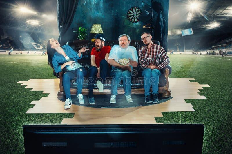足球足球迷坐沙发和观看的电视在橄榄球场中间 图库摄影