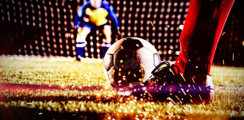 足球运动员的低部分有球的反对守门员 库存照片