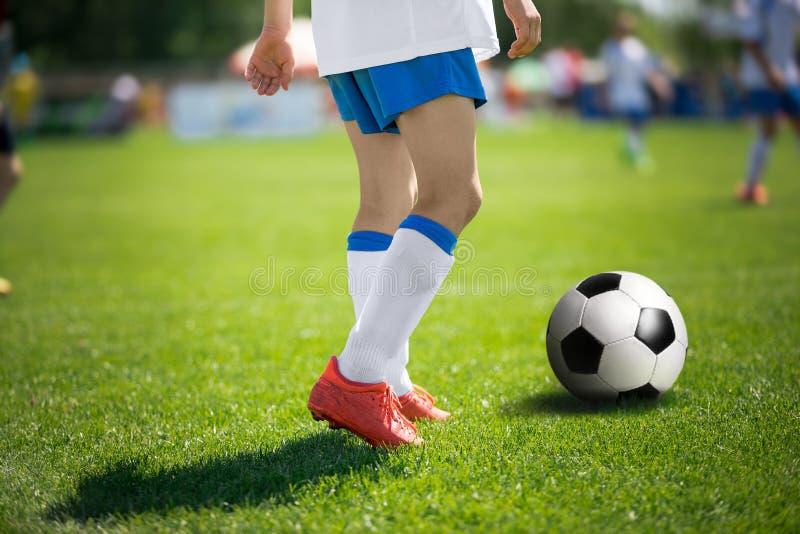 足球运动员的脚有足球的 足球运动员特写镜头 免版税库存照片