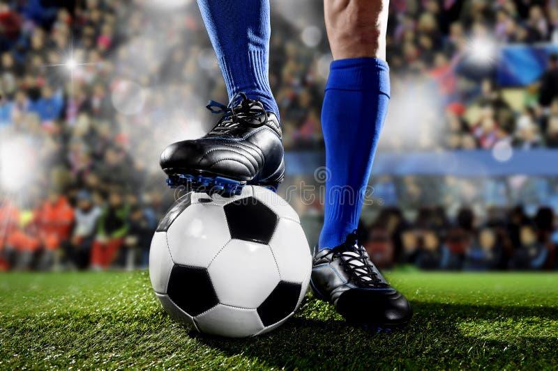 足球运动员的腿和脚蓝色站立与球的袜子和黑鞋子的参加比赛在足球场 免版税库存照片