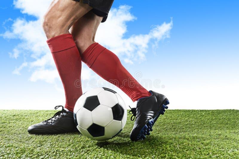 足球运动员的腿红色运行和滴下与球的袜子和黑鞋子的使用户外 免版税库存图片