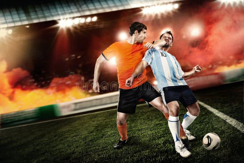 足球运动员踢了对面孔其他球员 免版税库存照片