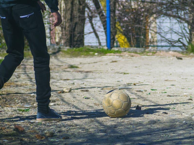 足球运动员` s腿和足球在领域 免版税库存图片