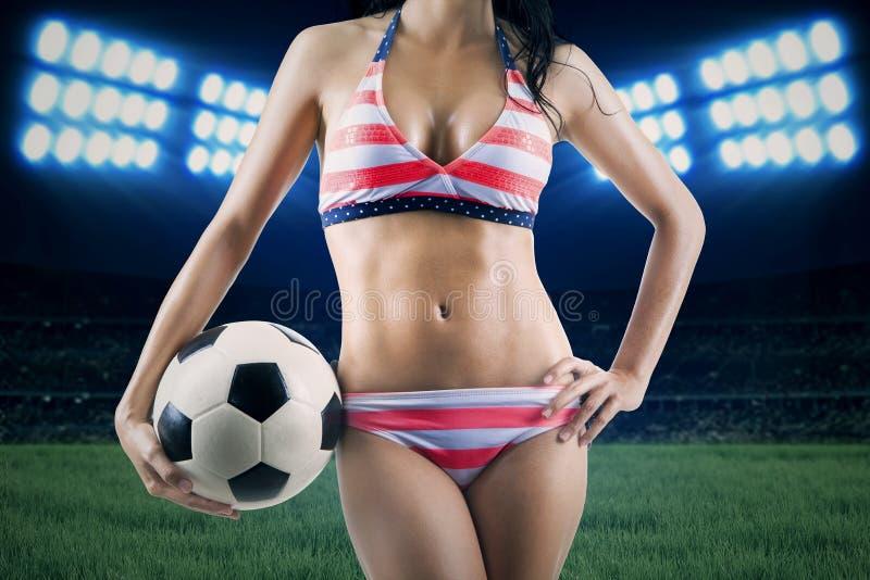 足球迷佩带的比基尼泳装和举行球 库存图片