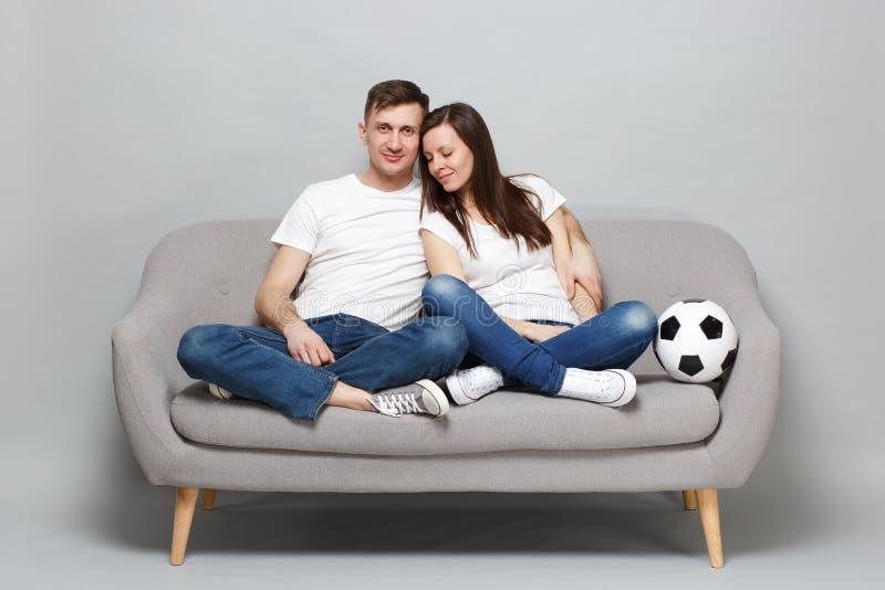 足球迷在白色T恤振作起来支持与足球的喜爱的队的俏丽的夫妇妇女人,拥抱隔绝了 免版税图库摄影