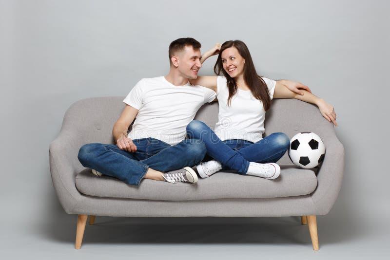 足球迷在白色T恤振作起来支持与足球的喜爱的队的快乐的夫妇妇女人,拥抱隔绝了 免版税库存照片