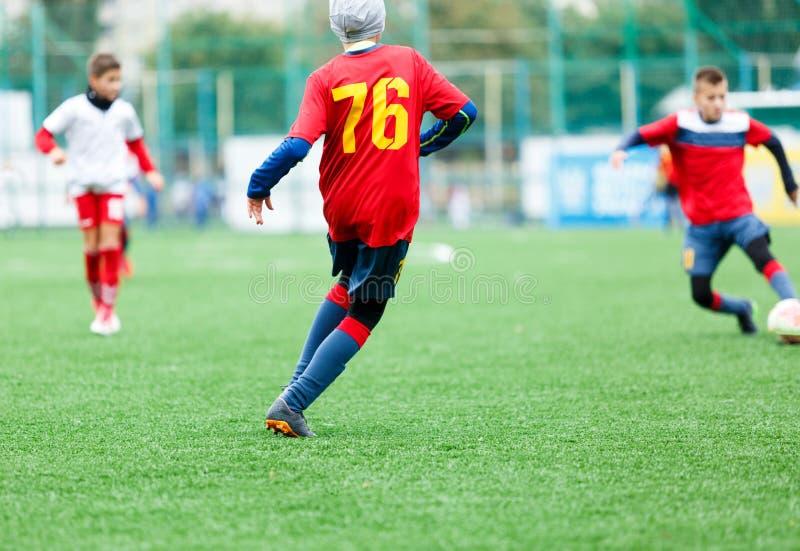 足球队-红色,蓝色,白色一致的戏剧足球的男孩在绿色领域 滴下的男孩 滴下的技能 免版税库存图片