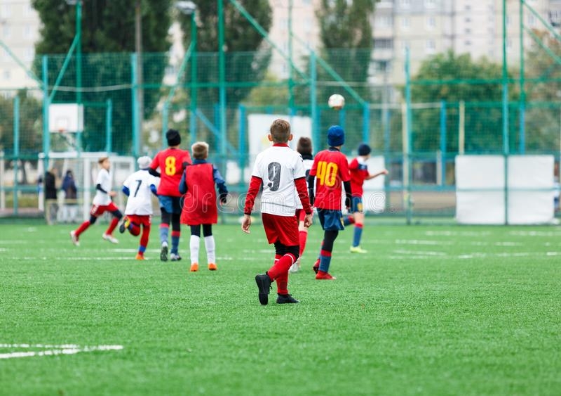 足球队-红色,蓝色,白色一致的戏剧足球的男孩在绿色领域 滴下的男孩 成队比赛,训练,活跃生活 免版税库存图片