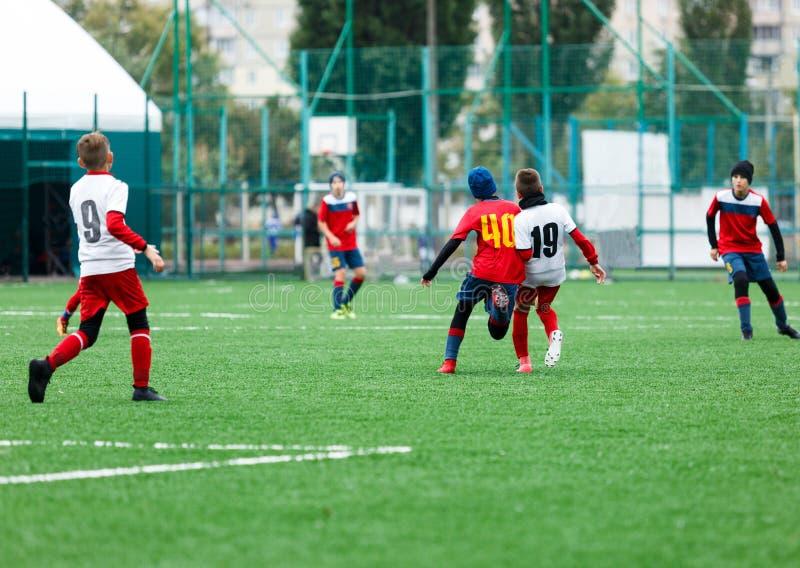 足球队-红色,蓝色,白色一致的戏剧足球的男孩在绿色领域 滴下的男孩 成队比赛,训练,活跃生活 免版税库存照片
