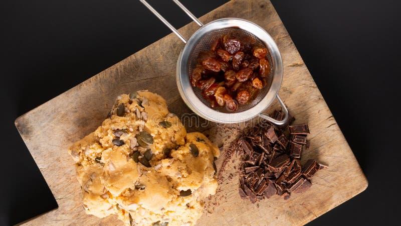 足迹健康食品概念自创未加工的面团与拷贝空间混合有组织的整体五谷在木板的能量曲奇饼 免版税库存照片