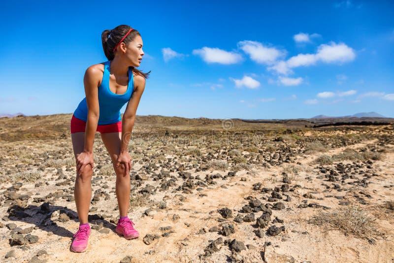 足迹赛跑者妇女疲倦了艰苦呼吸在超在困难的奔跑种族用尽的跑的心脏锻炼期间 亚裔年轻运动员 库存照片