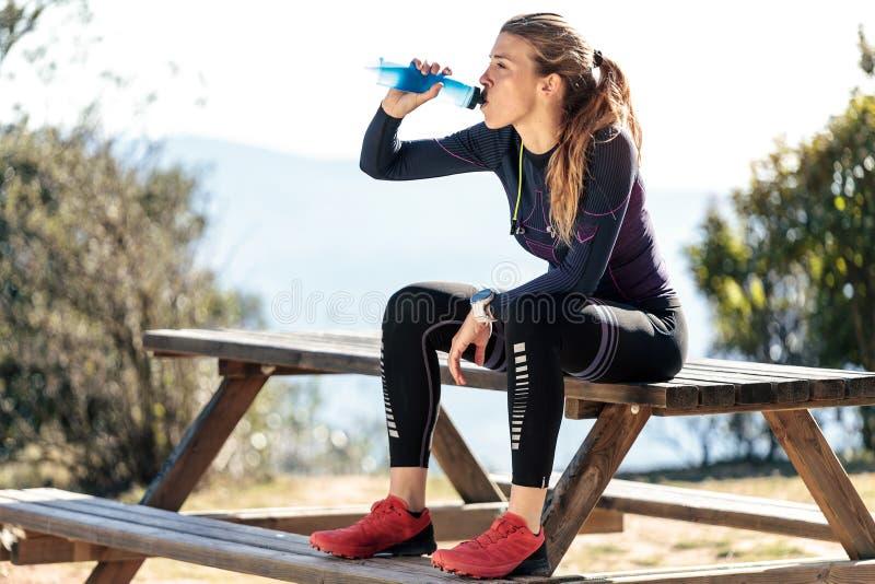 足迹赛跑者饮用水,当坐放松的一片刻长凳在山峰时 免版税图库摄影