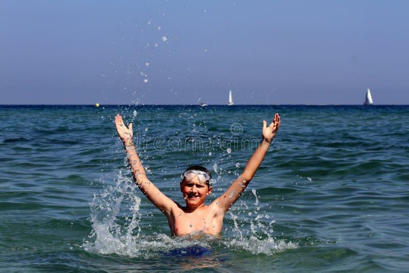 活跃男孩游泳在海 库存图片