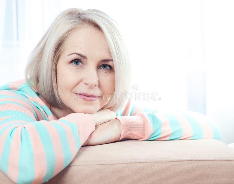 活跃美好中年妇女在家微笑友好和调查照相机 妇女的接近的表面s 库存照片
