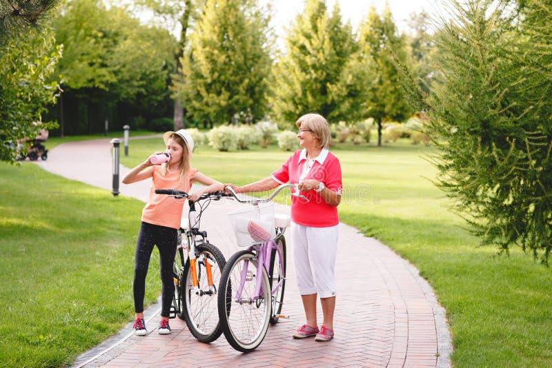 活跃资深妇女骑马自行车在公园 库存照片
