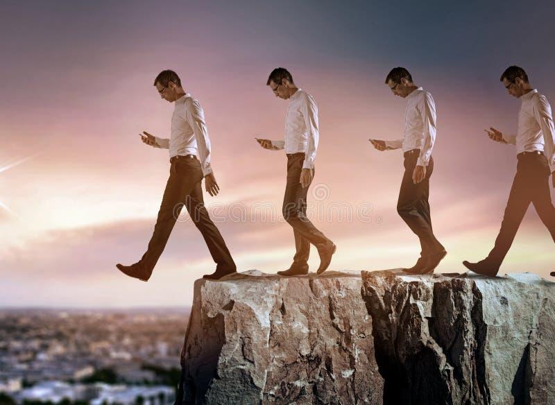 跌倒从峭壁的一个年轻商人的概念性画象 免版税库存照片