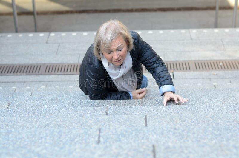 跌倒无能为力的资深的妇女跨步 免版税库存图片