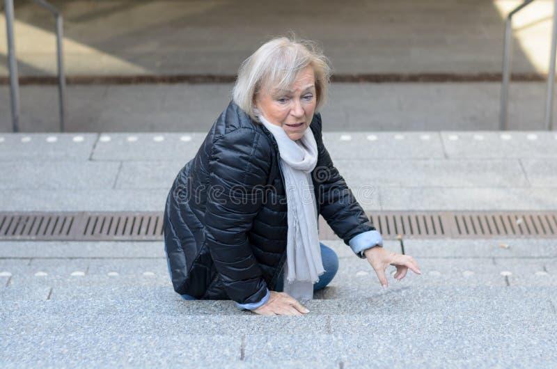 跌倒无能为力的资深的妇女跨步 库存图片