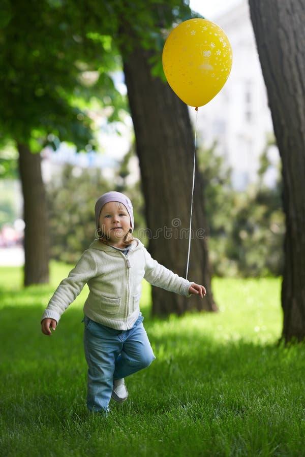 跑与一个黄色气球的愉快的孩子 免版税库存照片