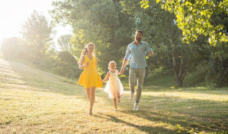 跑与他们逗人喜爱的女儿一起的两个愉快的父母 免版税图库摄影