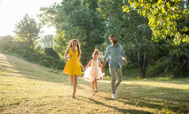 跑与他们逗人喜爱的女儿一起的两个愉快的父母 免版税库存图片
