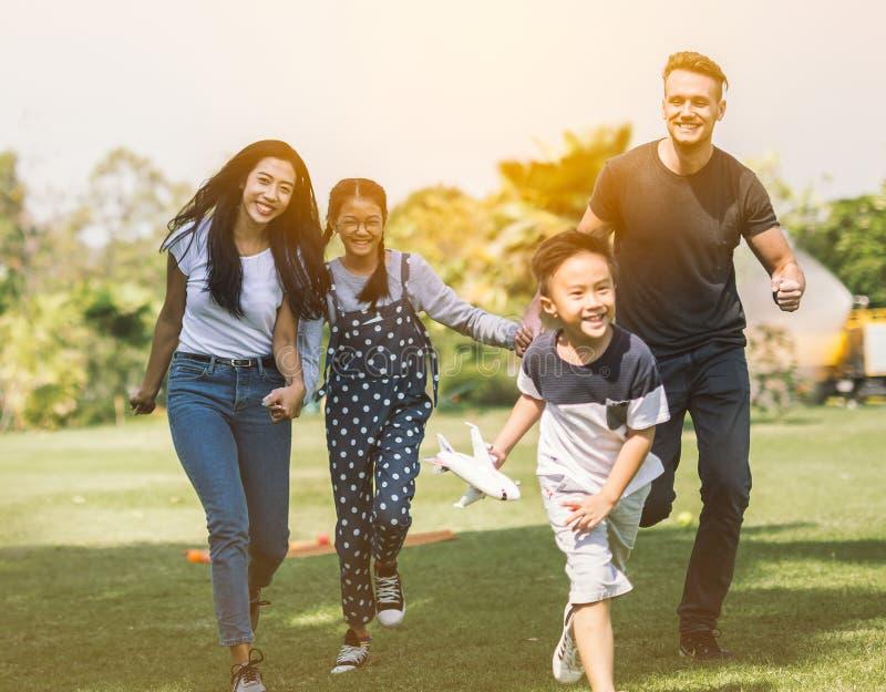 跑与儿子和女儿的家庭获得乐趣在夏天公园 免版税库存照片