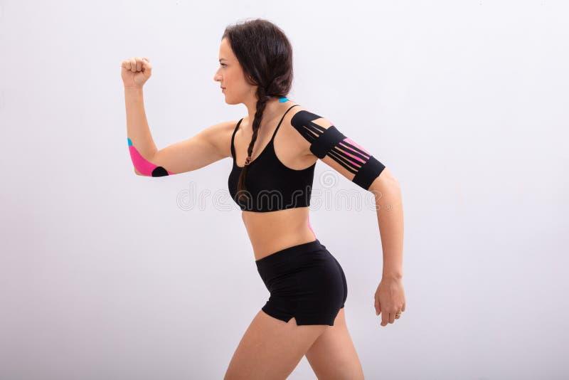 跑与在她的身体的理疗的磁带的妇女 免版税图库摄影