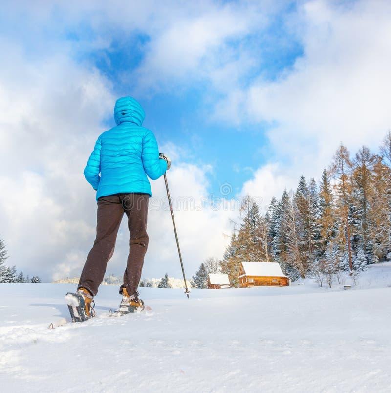 跑与在清楚的雪的雪靴的少妇 免版税库存照片