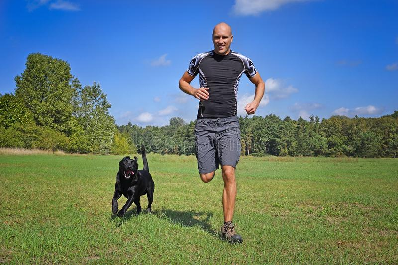 跑与狗的人 免版税库存图片