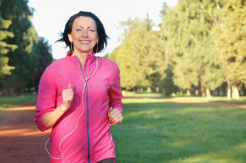 跑与耳机的年长妇女画象在公园 库存照片