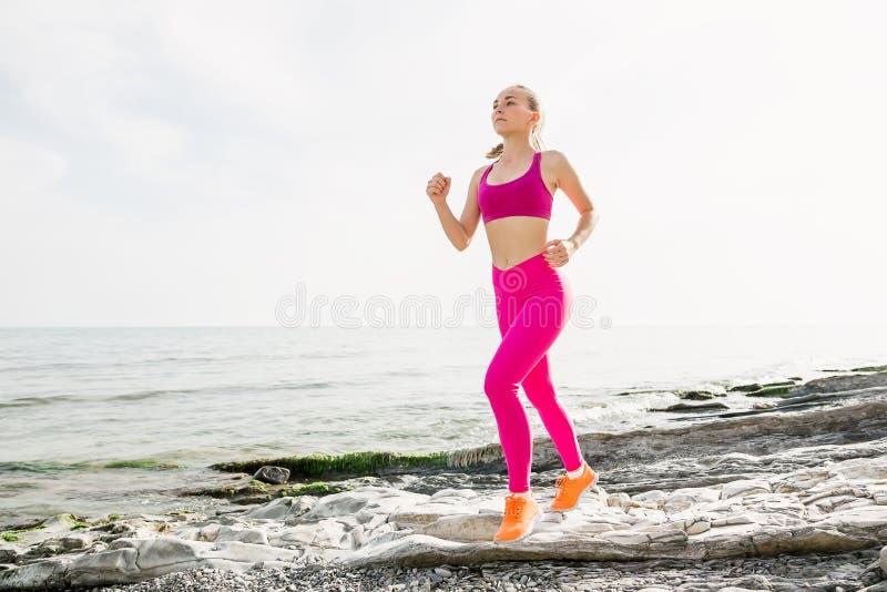 跑与背景的海洋的年轻可爱的健身女孩的图片 免版税库存图片