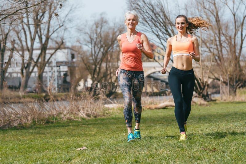 跑为体育的老和少妇在春日 免版税库存图片