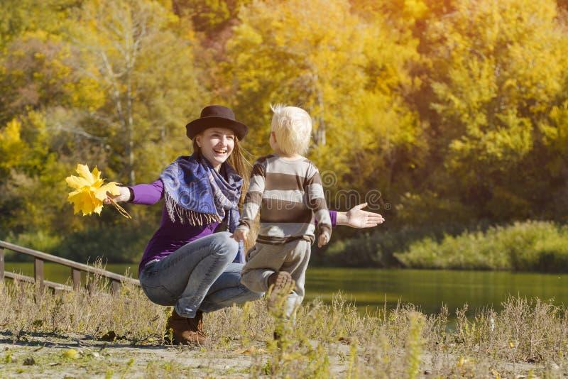 跑儿子的妈妈抓住 秋天,一个晴天 河岸 库存照片