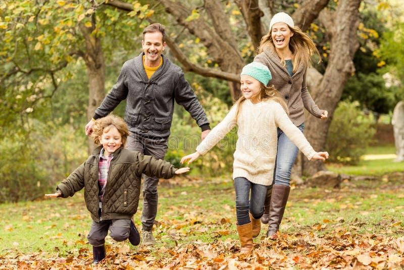 跑入叶子的微笑的年轻家庭 库存图片
