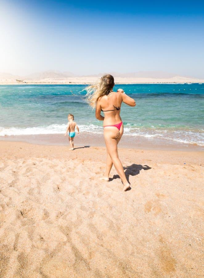 跑到她的小孩的年轻母亲的图象走在海 防止危险情况的充满爱心的父母在期间 库存图片