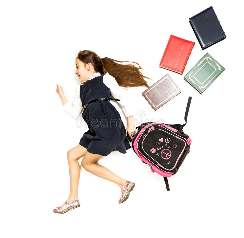 跑到有backp的学校的逗人喜爱的女小学生概念性照片 库存照片