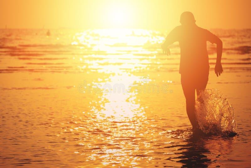 跑到海和水飞溅的孩子在与日落的夏天 免版税库存图片
