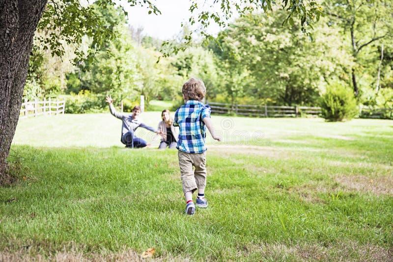 跑到父母的男孩 免版税图库摄影